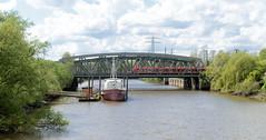 Fotos von Hamburgs Stadtteil Billbrook, Bezirk Hamburg Mitte. Blick  von der Bredowbrücke zur Bahnbrücke über den Tiedekanal; am Schiffsanleger der Feuerwehr-Akademie liegt ein Übungsboot.