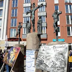 Ostermarsch 2019 - Demo für Abrüstung in Hamburg. politische Plakate vor den Bronzeskulpturen der Kreuzigungsgruppe vor der  Dreieinigkeitskirche von Hamburg St. Georg.