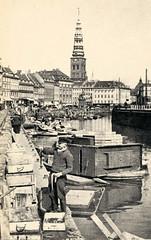 Fischer laden ihre Fischkisten für den Fischmarkt am Gammel Strand aus - im Hintergrund die Nikolaikirche.
