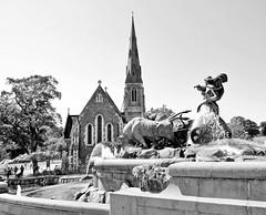 Schwarz-Weiss Aufnahme vom Gefion Brunnen in Kopenhagen; der Springbrunnen wird als Wunschbrunnen genutzt und zeigt Gefion, die Asenjungfrau aus der germanischen Mythologie und ihre zu Stieren verwandelten Söhne, welche mit einem Pflug eine Furche zw