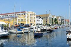 Gewerbe- und Wohnarchitektur am Christianshavns Kanal in Kopenhagen - Sportboote liegen an Holzpfählen.