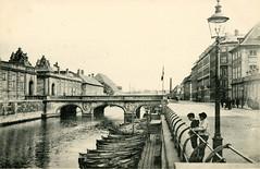 Historische Fotografie vom Frederiksholms Kanal in Kopenhagen, zwei Jungen stehen am Kanalgeländer bei einer Gaslaterne - Boote liegen am Steg. Blick zur Marmorbroen, lks. der Eingang zum Schloss Christiansborg.