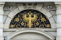 Detailbilder der Architektur Wiens - Türoberlicht mit schiedeeiserner Verzierung und goldenem Doppeladler.