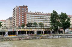 Mit buntem Graffiti versehene Mauern am Ufer des  Donaukanals in Wien - Blick auf die Wohnhausanlage Leopold Fige Hof am Franz-Josefs-Kai in Wien, errichtet 1967 - Areal des ehem. Hotels Métropole.