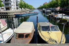 Sportboote liegen im Christianshavns Kanal von Kopenhagen - ein Fahrgastschiff mit Touristen fährt auf seiner Tour durch den Kanal.
