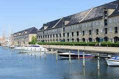 Historische Kasernenarchitektur / Magazine am Takkelloftsgraven in der dänischen Hauptstadt Kopenhagen - Sportboote, Motorboote liegen am Steg der Promenade.