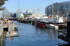 Moderne Wohnhäuser am Zollkanal / Tømmergraven im Kopenhagener Hafengebiet - Neubauten / Appartementhäuser am Wasser - Badegäste sitzen in der Sonne auf dem Holzsteg, Wasserpromenade - ein Kutter hat am Steg festgemacht.