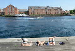 Holzterrasse an der Hafenpromenade von Kopenhagen laden zum Sitzen und sich Sonnen ein - am Ufer stehen alte Backstein-Lagerhäuser.