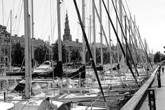 Sportboote / Segelboote in der Marina am Christianshavns Kanal in Kopenhagen - im Hintergrund der Spiral-Kirchturm Vor Freisers Kirke / Erlöserkirche.