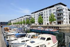 Sportboote liegen am Kai vom Christianshavns Kanal in Kopenhagen, ein Touristenschiff fährt Richtung Hafen. Moderne Neubauten säumen das Kanalufer am Hammershøis Kaj.