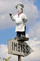 Fotos von Hamburgs Stadtteil Billbrook, Bezirk Hamburg Mitte. Hinweisschild zu einem Imbiss in der Bredowstraße, eine Koch-Figur mit Kochmütze und Schürze lädt zum Besuch der Kleingaststätte ein.