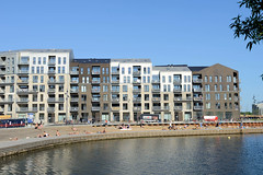 Terrassen - Promenade am Hafen von Kopenhagen - Menschen sitzen in der Sonne am Wasser - dahinter das Frederiksholm House - Wohnanlage mit 250 Wohnungen.