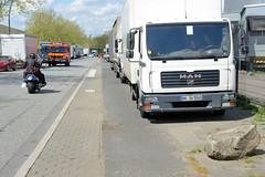 Fotos von Hamburgs Stadtteil Billbrook, Bezirk Hamburg Mitte - Gewerbegebiet mit parkenden Lastwagen auf einem ehemaligen Fußweg in der Bredowstraße, der Radweg ist asphaltiert.