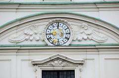 Detailbilder der Architektur Wiens - Fassadenschmuck, Stuckdekor - geflügelte Uhr mit goldenen Zeigern / Mond.