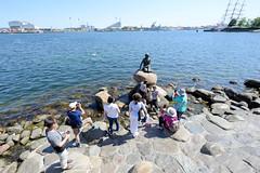 Touristen fotografieren sich und die Kleinen Meerjungfrau an der Uferpromenade Langelinie in Kopenhagen. Bronzefigur nach dem Vorbild in dem gleichnamigen Märchen des dänischen Dichters Hans Christian Andersen; Bildhauer Edvard Eriksen, 1913.
