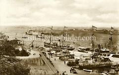 Alte Fotografie vom Hafengebiet in Kopenhagen - Frachtschiffe liegen am Kai, an Land ist Fracht gestapelt - Pferdefuhrwerke mit Ladung.