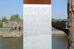 Fotos vom Hamburger Stadtteil Finkenwerder, Bezirk Hamburg Mitte - Gedenktafel am Ufer des Rüschkanals mit beschreibenden Text zu den dahinter liegenden ehemaligen U-Boot Bunkern der deutschen Werft.