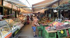 Touristen und Einheimische bummeln über den Wiener Naschmarkt. Der Naschmarkt ist mit seinem Angebot von  Obst, Gemüse, Backwaren, Fisch und Fleisch  der größte innerstädtische Markt der Stadt, darüber hinaus gibt es eine größere Anzahl von Gastronom