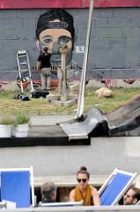 Ein Graffiti-Künstler arbeitet an einem Portrait an der Kaimauer vom Donaukanal in Wien.