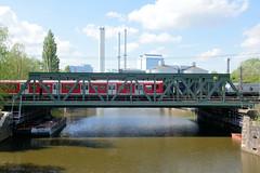 Fotos von Hamburgs Stadtteil Billbrook, Bezirk Hamburg Mitte. Eine S-Bahn überquert die Bahnbrücke über den Tiefstackkanal, im Hintergrund das Kraftwerk Tiefstack.