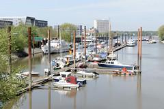Fotos vom Hamburger Stadtteil Finkenwerder, Bezirk Hamburg Mitte -    Anleger mit Sportbooten und Arbeitsschiffen im Steendiekkanal. Früher war der Kanal Teil der deutschen Werft, die dort Ufer der Elbe Schiffe baute; Im Hintergrund ist das ehemalige