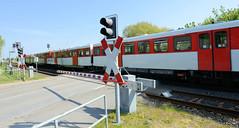 Fotos aus der Gemeinde Bönnigstedt - Kreis Pinneberg - Metropolregion Hamburg. Geschlossener Bahnübergang / Schranken an der Bönningstedter Bahnhofstraße, ein Zug der AKN passiert den Übergang.