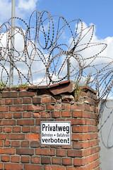 Fotos  aus dem Hamburger Stadtteil Rothenburgsort - Bezirk Mitte. Ziegelmauer mit Stacheldraht gesichert - Schild Privatweg Betreten und befahren verboten.