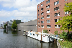 Fotos aus dem Hamburger Stadtteil Hamm - Bezirk Mitte. Blick von der ersten Grevenbrücke / Grevenweg auf einen Wohnblock mit Balkons und Gewerbegebäude am Mittelkanal, ein Industriekanal von Hamburg-Hamm; ein Hausboot liegt am Kanalufer.