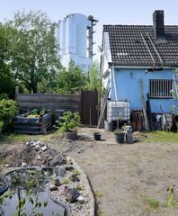 Fotos  aus dem Hamburger Stadtteil Rothenburgsort - Bezirk Mitte. Einzelhaus mit Spitzdach/Satteldach auf dem Gelände des Gartenbauverein Bahnhof Tiefstack am Langen Hagen; im Hintergrund ein Betonsilo.