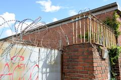 Fotos  aus dem Hamburger Stadtteil Rothenburgsort - Bezirk Mitte. Metalltor und Ziegelmauer mit Stacheldraht gesichert,