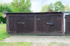Fotos  aus dem Hamburger Stadtteil Rothenburgsort - Bezirk Mitte. Garagen mit Holztoren an der Billstraße - Verbotsschild für kackende Hunde.