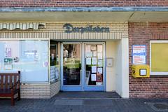 Bilder aus Wöhrden, Gemeinde im Kreis Dithmarschen - Metropolregion Hamburg. Wöhrdener Dörpsladen - Fassade mit gelben Ziegeln und Eingangstür / Doppeltür im Baustil der 1960er Jahre.