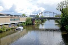 Fotos  aus dem Hamburger Stadtteil Rothenburgsort - Bezirk Mitte. Blick von der Schurzalleebrücke auf den Billkanal und die Brücke der Gustav Kunst Straße; ein Sportboot / Motorboot liegt am Steg einer Lagerhalle.