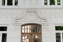 Bilder aus dem Hamburger Stadtteil Hoheluft Ost - Bezirk Hamburg Nord. Hauseingang mit Reliefportal in der Husumer Straße - denkmalschütztes Etagenhaus, errichtet 1909 - Architekt Heinrich Mandix.