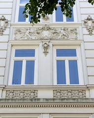 Architekturfotos aus dem Hamburger Stadtteil Eimsbüttel - Bezirk Eimsbüttel; mit Reliefschmuck und Putten versehene Hausfassade im Henriettenweg.