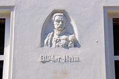 Fotos aus dem Hamburger Stadtteil Hoheluft West, Bezirk Hamburg Eimsbüttel. Fassadenrelief mit Büste von Blücher mit Orden  - Schriftzug Blücher-Heim; Etagenhaus.