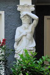 Fotos aus dem Hamburger Stadtteil Hoheluft West, Bezirk Hamburg Eimsbüttel. Männliche Figur als Teil einer Säule / Stütze - Fassadeschmuck, Bauschmuck der Gründerzeit.