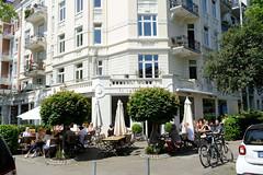 Bilder aus dem Hamburger Stadtteil Hoheluft Ost - Bezirk Hamburg Nord. Eckgebäude der Gründerzeit - Abendrothsweg / Meldorfer Straße - die Ladenräume werden als Café mit Aussengastronomie genutzt.