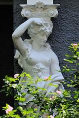 Fotos aus dem Hamburger Stadtteil Hoheluft West, Bezirk Hamburg Eimsbüttel. Weibliche nackte Figur als Teil einer Säule / Stütze - Fassadeschmuck, Bauschmuck der Gründerzeit.