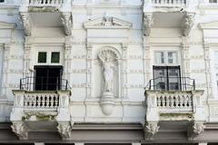 Architekturfotos aus dem Hamburger Stadtteil Eimsbüttel - Bezirk Eimsbüttel; Gründerzeitgebäude in der Margaretenstraße. Denkmalgeschütztes Mehrfamilienhaus - Fassadendekoration mit Skulptur, errichtet 1887 - Architekt A. A. F. Nissen.