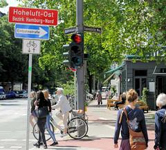 Bilder aus dem Hamburger Stadtteil Hoheluft Ost - Bezirk Hamburg Nord. Stadtteilgrenze, Stadtteilschild Hoheluft Ost an der Kreuzung Lehmweg, Eppendorfer Weg - Passanten.