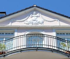Architekturfotos aus dem Hamburger Stadtteil Eimsbüttel - Bezirk Eimsbüttel; Schmuckgiebel - Putte mit Blumengirlande reitet Schwein - Mehrfamilienhaus mit Laden einer ehem. Schlachterei. Das Gebäude wurde 1910 errichtet - Architekt Wilhelm Brünecke;