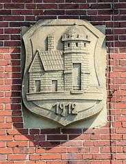 Bilder von der historischen Hansestadt Fürstenau im Landkreis Osnabrück - Bundesland Niedersachsen;  Steinrelief / Wappen mit Jahreszahl 1912 an der Fassade der alten Volksschule in der Bahnhofstraße.