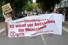 Swarming-Aktion der Extinction Rebellion Gruppe Hamburg Winterhude am Moorfuhrtweg; DemonstrantInnen halten ein Transparent quer über die Straße: Eilmeldung - EU warnt vor Aussterben der Menschheit.