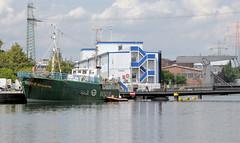 """Das ehem. Rettungsschiff  Sea-Eye hat am Lotsenkanal im Hafen von Hamburg Harburg festgemacht; im Hintergrund die schwimmende Harburger Flüchtlingsunterkunft """"Transit""""."""