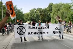 """Swarming-Aktion der Extinction Rebellion Gruppe Hamburg Winterhude am Moorfuhrtweg; DemonstrantInnen halten Transparent  von Extinction Rebellion quer über die Straße: Klimawande = Massensterben. © <a href=""""http://www.christoph-bellin.de/fo"""