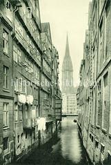 Historische Motive aus der Hansestadt Hamburg - alte Bilder aus Hamburgs Altstadt. Blick durch das Stöckelhornfleet zum Nikolaifleet und dem Kirchturm der Sankt Nikolaikirche; Wäsche hängt zum Trocknen vor den Fenstern.