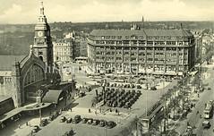 Historische Darstellungen vom Hamburger Hauptbahnhof im Stadtteil Sankt Georg; Luftaufnahme vom Bahnhofsgebäude und dem Hachmannplatz auf dem parkende Taxis stehen, dahinter das Bieberhaus.