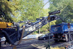 Bilder aus dem Hamburger Stadtteil Dulsberg - Bezirk Hamburg Nord. Straßenbauarbeiten im Alten Teichweg -  eine Asphalt-Straßen-Fräsmaschine trägt den Asphalt ab und fördert den Straßenbelag per Förderband auf einen bereitstehenden Lastwagen.