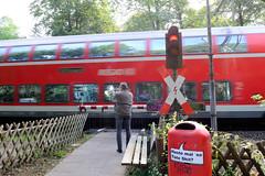 Marienthal ist ein Hamburger Stadtteil im Bezirk Hamburg Wandsbek. Bahnübergang für Fußgänger am Schlossgraben in Hamburg Wandsbek; die Ampel zeigt rot, die ist Schranke heruntergelassen - ein Fußgänger wartet davor während ein Zug vorbeirauscht